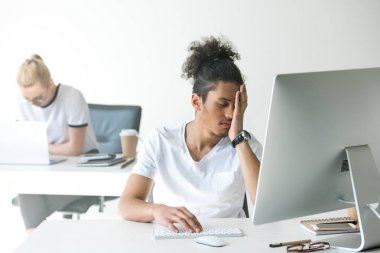 tired young african american man working with desktop computer in office