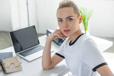 beautiful young woman looking at camera while working with laptop in office