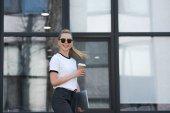 Fotografie krásná mladá žena v sluneční brýle se usmívá na kameru podržíte pohárek a laptop mimo kancelářská budova