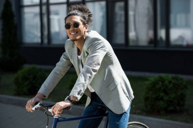 Stylish young african american man in sunglasses sitting on bicycle and smiling at camera stock vector