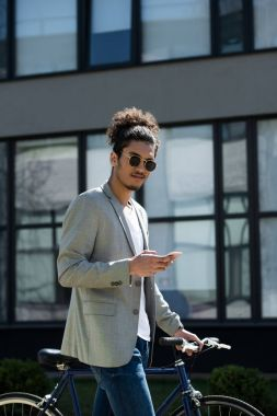 young african american man looking at camera while standing with bicycle and using smartphone
