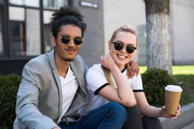 young multiethnic couple in sunglasses smiling at camera while drinking coffee to go on street