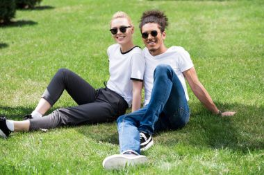 happy young multiethnic couple in sunglasses sitting together on grass and smiling at camera
