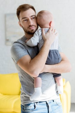 young father holding infant baby boy at home
