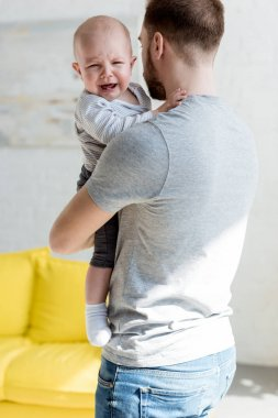 father with little crying son at home