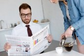 Photo businessman in eyeglasses reading economics newspaper while wife pouring coffee in cup on kitchen