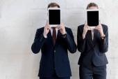 podnikatelé v formální oblečení drží digitální tablety s prázdnými obrazovkami