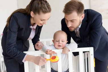 happy businesspeople playing with little son in baby crib at home