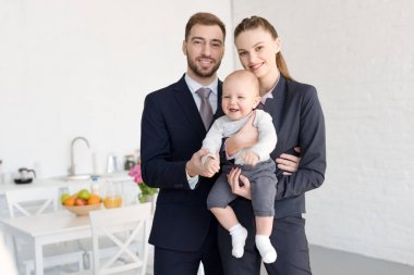 happy businesspeople in formal wear holding little son at home