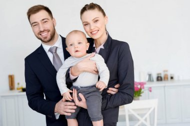 smiling business couple with little son at home