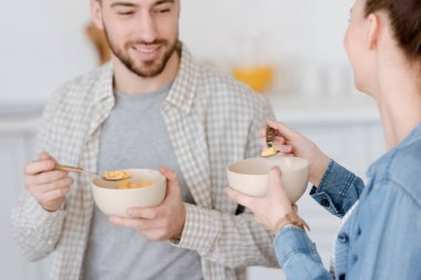 young couple eating corn flakes for breakfast