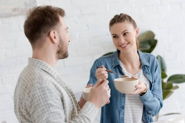 young couple eating corn flakes for breakfast in morning