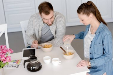 husband and wife having breakfast with corn flakes and coffee in kitchen with digital tablet