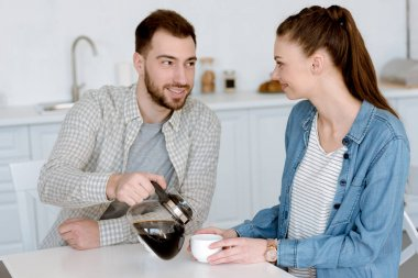 boyfriend pouring coffee for girlfriend in kitchen