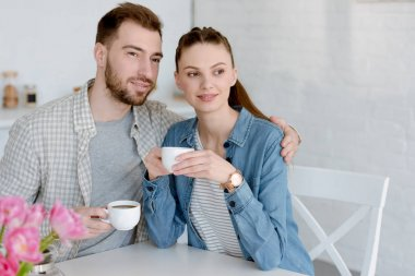 happy couple with coffee cups sitting together on kitchen in morning