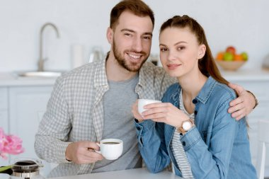 smiling couple with cups of coffee sitting on kitchen
