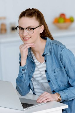young female freelancer working with laptop on kitchen