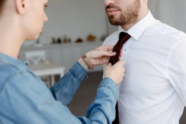 young wife wearing a tie on businessman at home