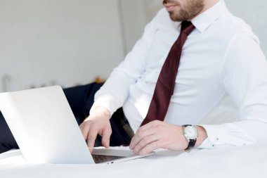 cropped view of businessman using laptop on bed