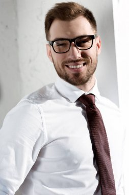 smiling businessman in eyeglasses looking at camera
