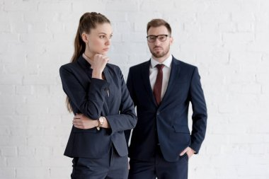 confident businessman and pensive businesswoman posing near white wall