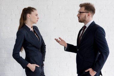 serious businessman and businesswoman in suits discussing near white wall
