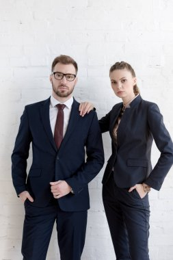 confident businesspeople posing together near white wall