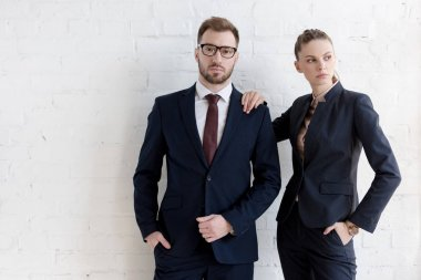 confident business coworkers posing together near white wall