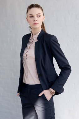 beautiful confident businesswoman in suit posing near white wall