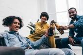 lächelnde multikulturellen jungen Freunde klirrende Flaschen Bier