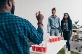 Fotografie oříznutý obraz africký americký mladík chystá hodit míč v beer pong hry