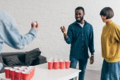 Fotografie cropped image of multiethnic group of friends playing beer pong at table