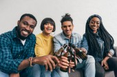 vier lächelnd multikulturellen Freunde sitzen und klirrende Flaschen Bier