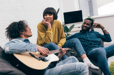 mixed race man playing on acoustic guitar to multiethnic friends on couch