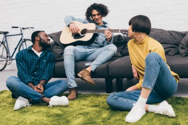 young mixed race man playing on acoustic guitar to friends