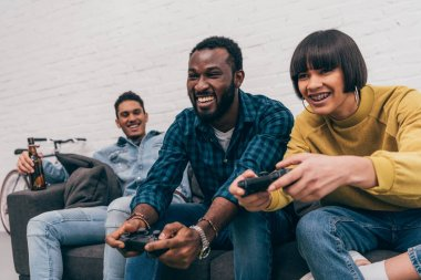 smiling african american man and mixed race woman with joysticks playing video game and young man sitting behind on couch with bottle of beer