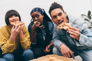 smiling multicultural group of friends eating pizza and watching match