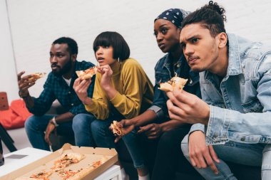 group of young multiethnic friends eating pizza and watching match