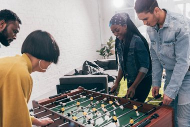group of young multiethnic friends playing table football