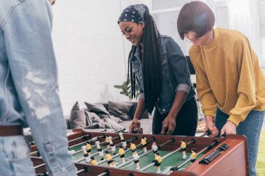 cropped shot of young multiethnic friends playing table soccer