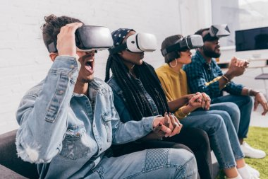 group of young multicultural friends using virtual reality headsets