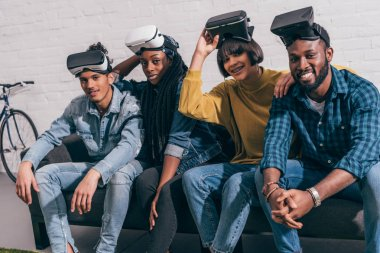 young multicultural friends with lifted up virtual reality headsets