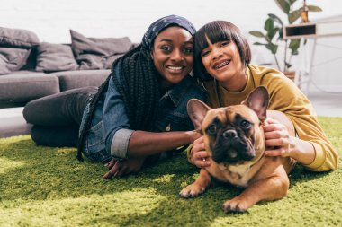 two young multicultural female friends laying on rug with french bulldog