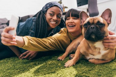young multicultural female friends taking selfie with french bulldog