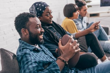 laughing african american man holding ball and watching american football match with friends on couch