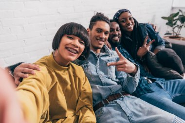 young mixed race woman taking selfie with multiethnic friends doing peace gesture