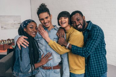 portrait of young smiling group of multiethnic friends embracing each other