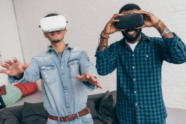 smiling young male friends using virtual reality headsets