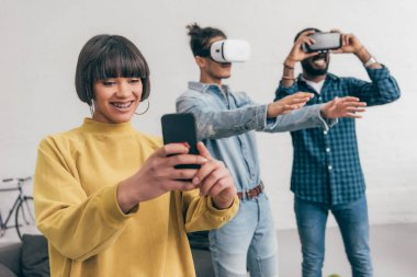 smiling mixed race young woman with smartphone and two men using virtual reality headsets behind