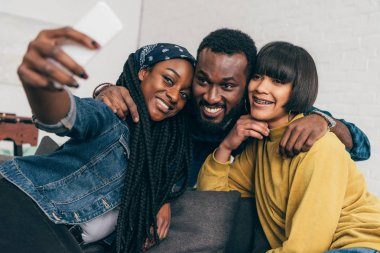 smiling black woman taking selfie with two multiethnic friends